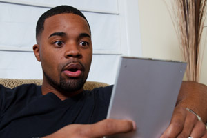 Man reading an eBook and looking surprised